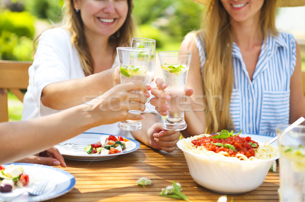 Happy female friends with glasses of lemonade at dining table in Stock photo © dashapetrenko