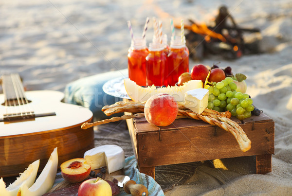 Picnic on the beach at sunset with fruits and juices  Stock photo © dashapetrenko