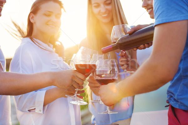 Group of happy friends having red wine on the beach Stock photo © dashapetrenko