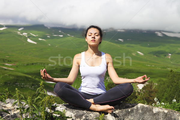 Attractive young woman doing a yoga pose for balance on top of h Stock photo © dashapetrenko