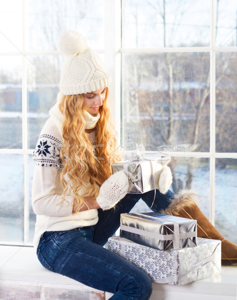 Young happy blond woman looking at Christmas presents Stock photo © dashapetrenko