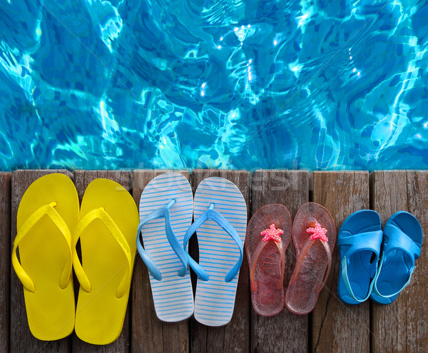 Brightly colored flip-flops on wooden background near the pool Stock photo © dashapetrenko