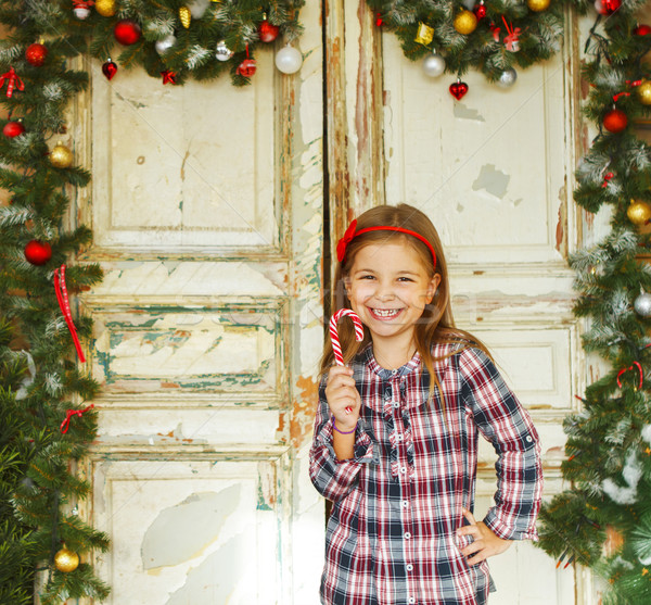 Happy little girl holding Christmas candy cane Stock photo © dashapetrenko