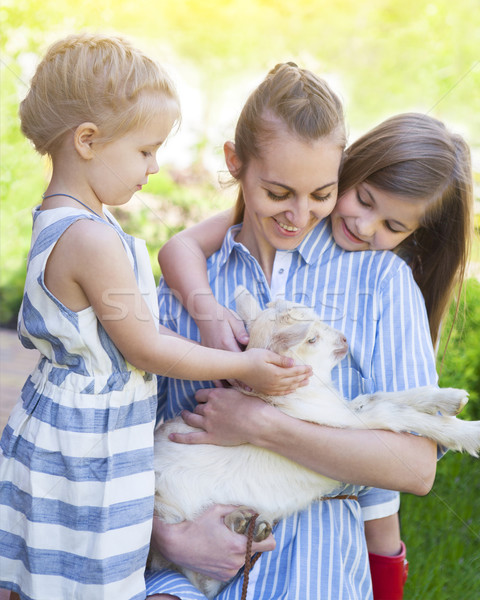 Happy mother and her daughters with baby goats  Stock photo © dashapetrenko