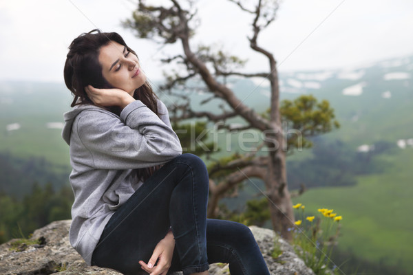 Dreaming girl sits on the edge of the cliff  Stock photo © dashapetrenko