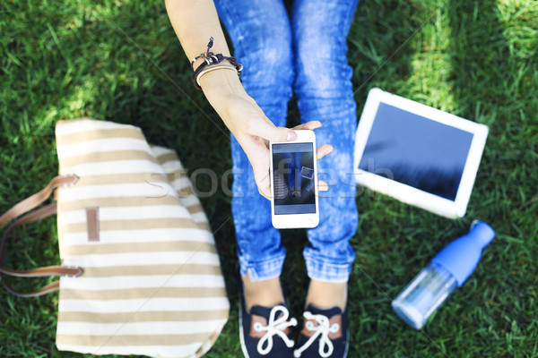 Mobile phone in a hand of girl on a green grass  Stock photo © dashapetrenko
