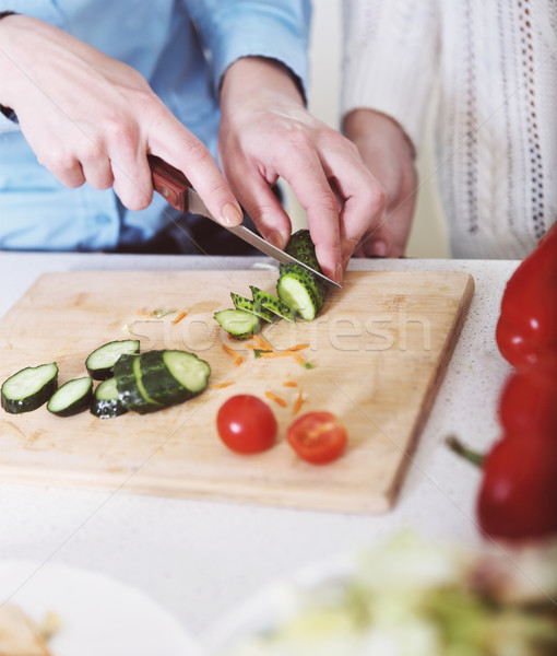 Stock photo: Closeup of hands of a woman cooking vegetables salad