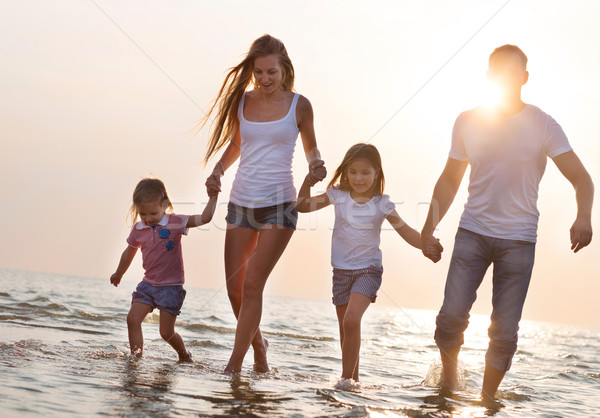 Stock photo: Happy young family having fun running on beach at sunset