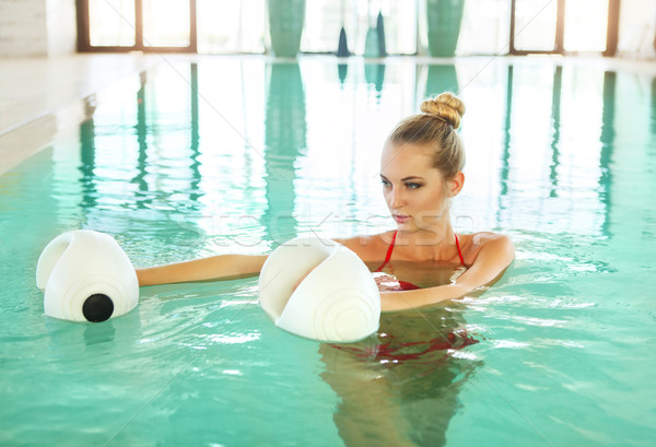 Blond woman doing aqua aerobics with foam dumbbells in swimming  Stock photo © dashapetrenko
