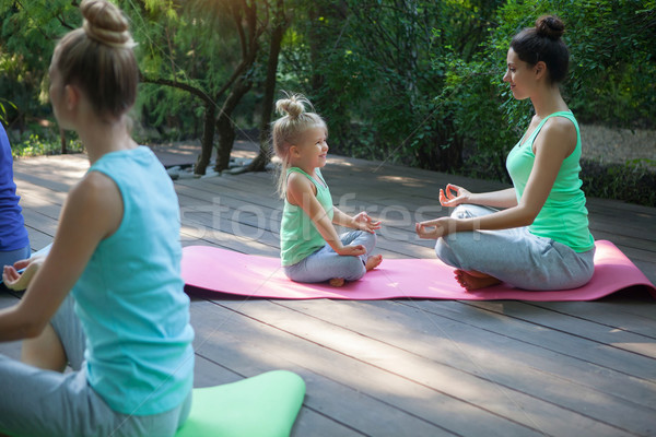 Group of mothers and daughters doing exercise practicing yoga ou Stock photo © dashapetrenko
