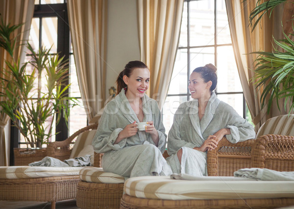 Two young happy women drinking tea at spa resort Stock photo © dashapetrenko