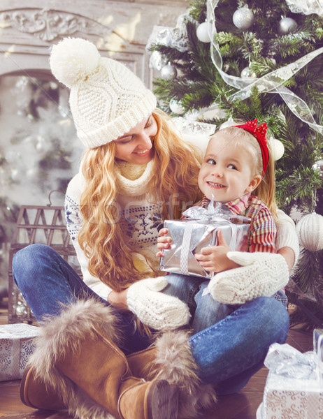 Happy mother and her baby daughter by the Christmas tree Stock photo © dashapetrenko