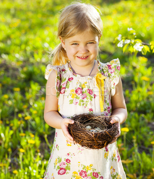 Stock photo: Little girl holding an Easter eggs in the nest