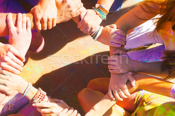 Friends putting their hands together in a sign of unity and team