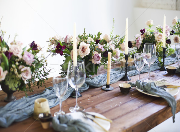 Bouquets of pink flowers on a table set for dinner with candles Stock photo © dashapetrenko