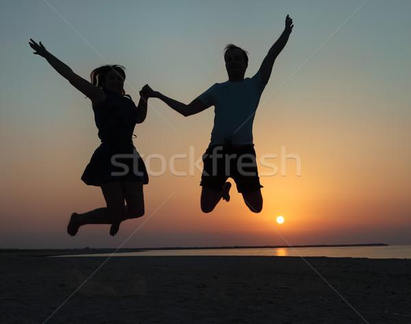 Siluetă cuplu om femeie jumping plajă Imagine de stoc © dashapetrenko