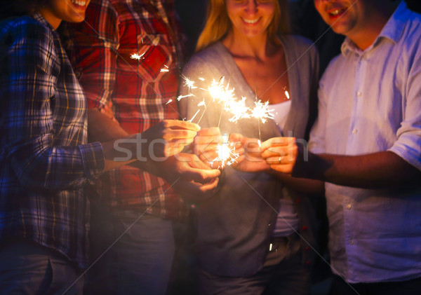 Young people with sparklers having fun on outdoor party Stock photo © dashapetrenko