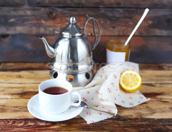 Cup of black tea with a lemon, teapot and jam  Stock photo © dashapetrenko