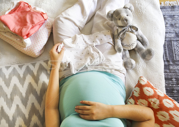 Pregnant woman is packing baby clothes  Stock photo © dashapetrenko