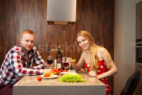 Happy couple in a kitchen eating pasta in a kitchen Stock photo © dashapetrenko
