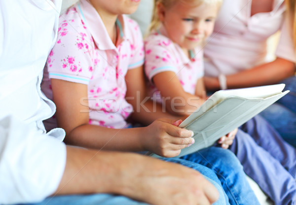 Happy family of mother, father and daughters using a tablet comp Stock photo © dashapetrenko