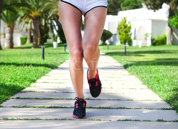 Runner feet running on road in the park  Woman fitness