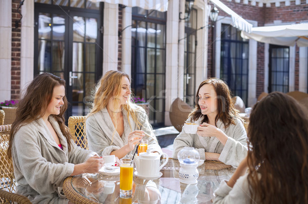 Four young women drinking tea at spa resort Stock photo © dashapetrenko