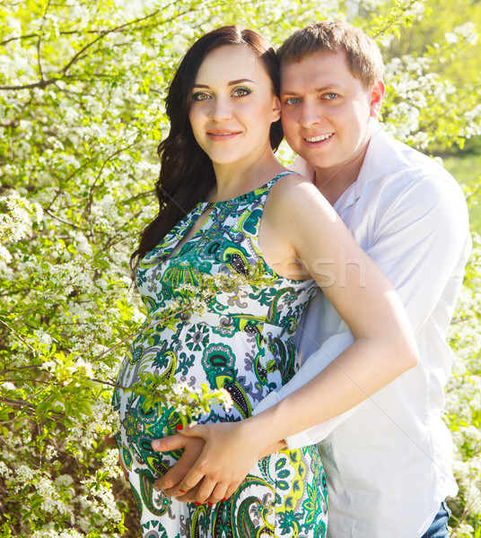 Young happy pregnant couple in the flowering spring park Stock photo © dashapetrenko
