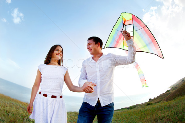 Stock photo: Happy young couple in love with flying a kite
