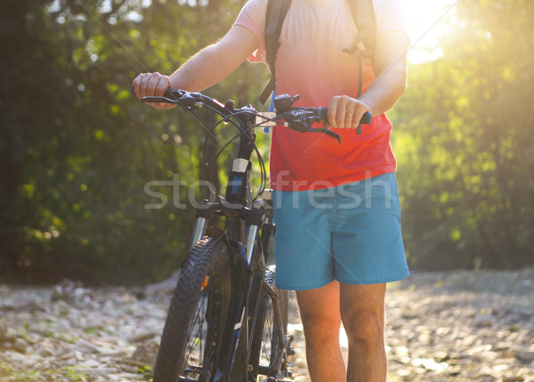 Young man with bicycle by mountain river Stock photo © dashapetrenko