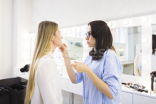 Young makeup artist doing makeover to pretty model Stock photo © dashapetrenko