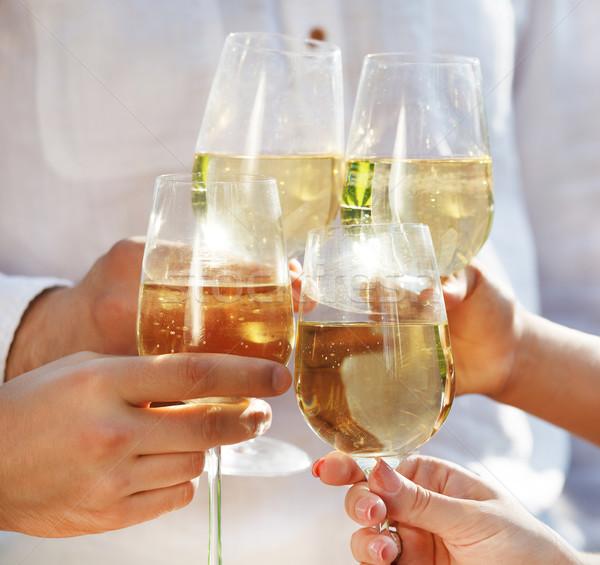 People holding glasses of white wine making a toast Stock photo © dashapetrenko