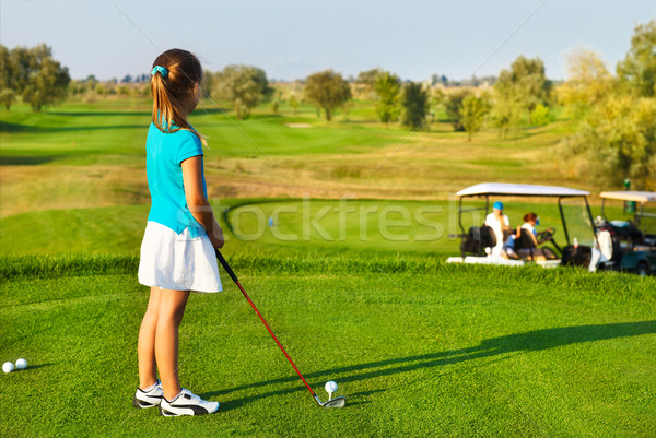 Stock photo: Cute little girl playing golf on a field outdoor