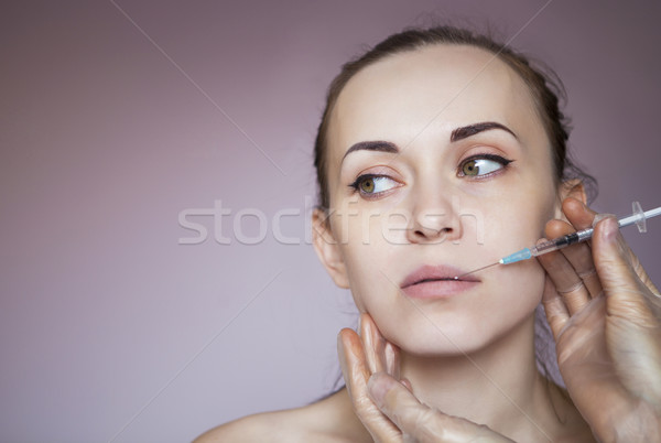 Young pretty woman getting cosmetic injection in the face Stock photo © dashapetrenko