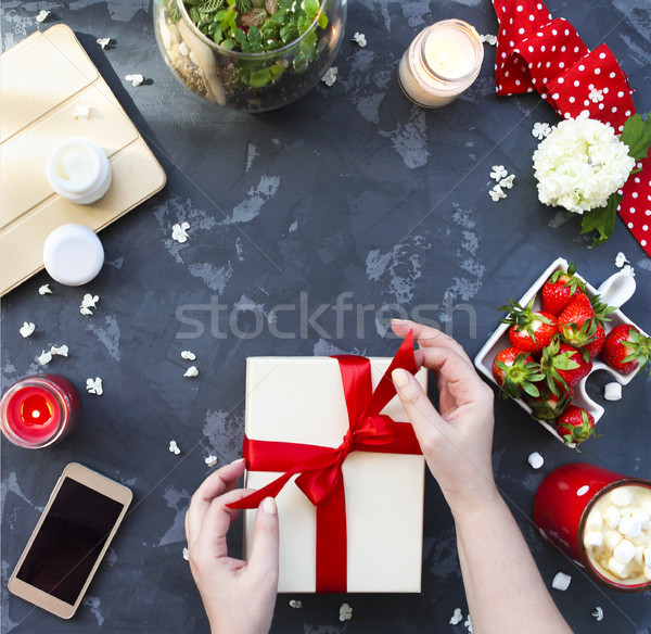 Stock photo: Young woman packing present with red ribbon. Top view