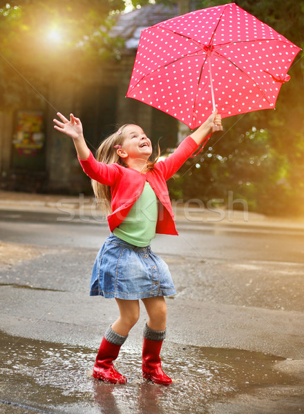 Child with polka dots umbrella wearing red rain boots  Stock photo © dashapetrenko