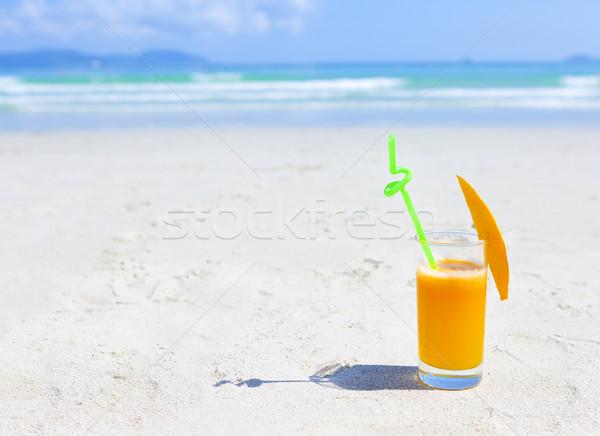 Glass of orange colour juice and sand and sea Stock photo © dashapetrenko