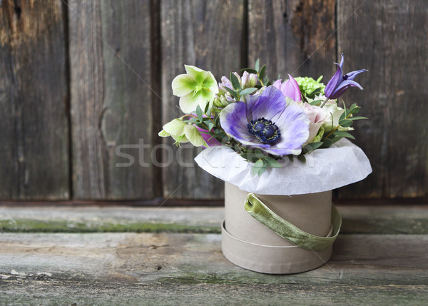 Bouquets of pink and violet flowers in the box on a woden backgr Stock photo © dashapetrenko