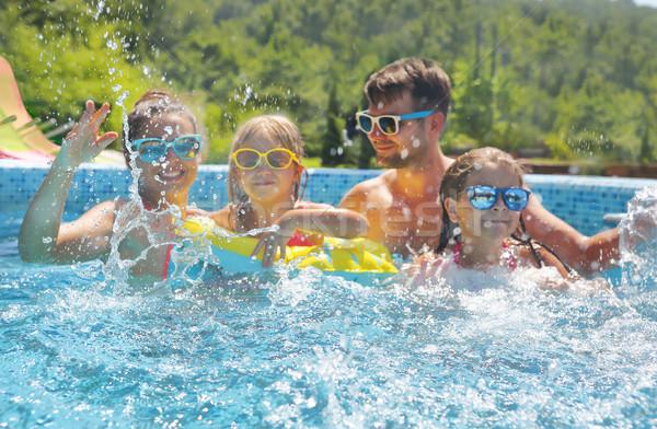 Happy family with two kids having fun in the swimming pool.  Stock photo © dashapetrenko