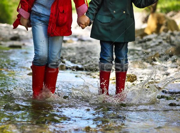 Child wearing rain boots jumping. Close up Stock photo © dashapetrenko