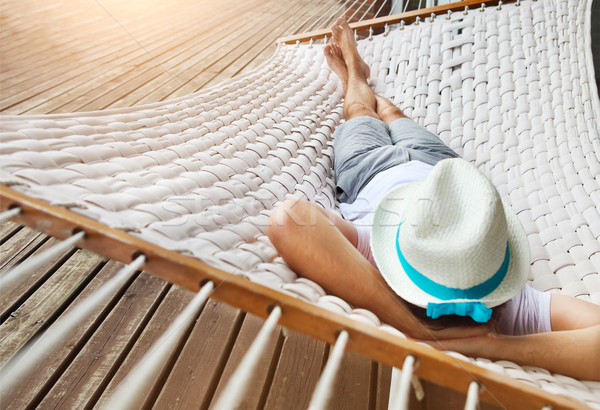 Man in hat in a hammock on a summer day Stock photo © dashapetrenko