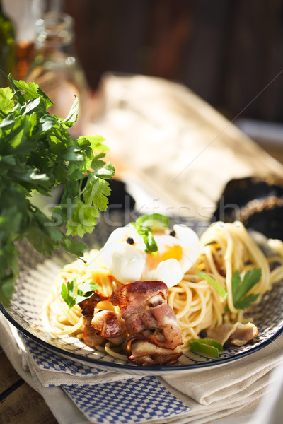 Nicely served spaghetti carbonara on black background  Stock photo © dashapetrenko