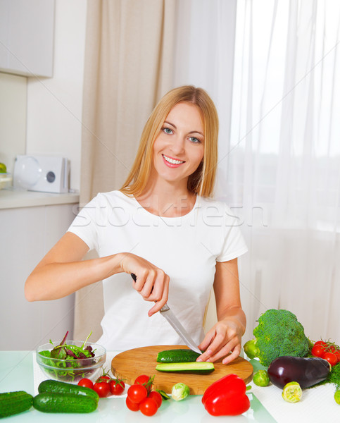 Young woman cutting vegetables at the kitchen Stock photo © dashapetrenko