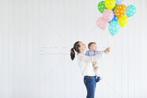 Little boy with his mom holding a bunch of colored balloons Stock photo © dashapetrenko