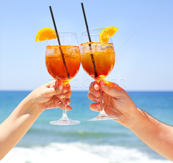 Two cocktail glasses in the hands on sea background Stock photo © dashapetrenko