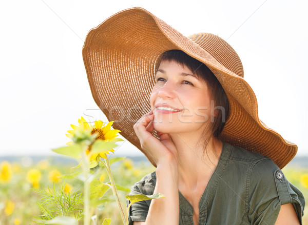 Stock photo: Portrait of a young smiling woman with sunflower