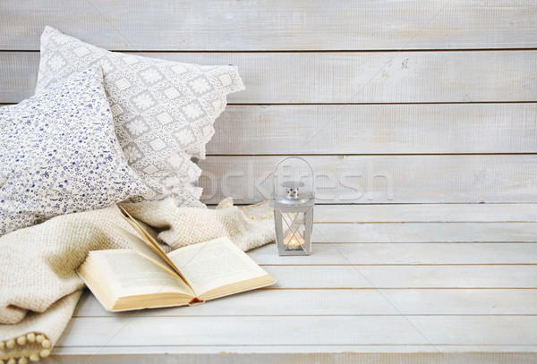 Cozy still life with lantern, pillows, book and plaid  Stock photo © dashapetrenko