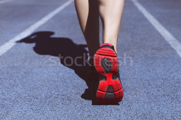 Athlete runner feet down stadium track. Closeup on female shoe a Stock photo © dashapetrenko
