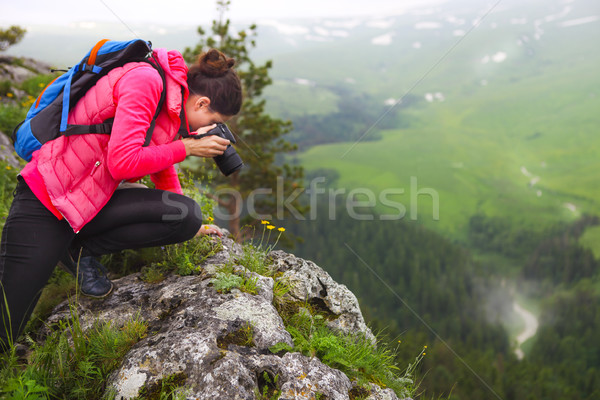 Woman with camera making photo on mountain peak Stock photo © dashapetrenko