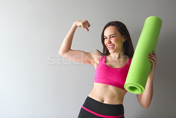 Stock photo: Attractive woman wearing pink sportswear holding green yoga or f